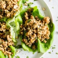 These Thai ground chicken lettuce cups are a super simple dinner that is packed full of flavor and perfect for a light summer dinner. Ground chicken mixed with ginger, lemongrass, fish sauce, soy sauce and sprinkled with chopped peanuts and lots of cilantro. You'll love these lettuce cups!