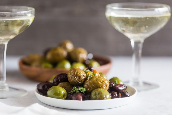 These garlic herb roasted olives are the perfect snack food! They are salty, packed full of garlic, thyme and orange flavor and are ready in just 15 minutes! They pair perfectly with prosecco and will be sure to impress all the olive lovers in your life.