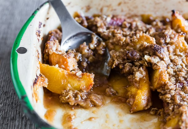 ginger peach crisp in a metal dish with spoon
