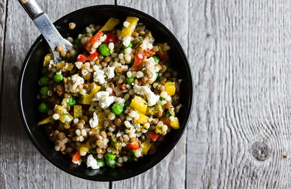 This lentil couscous goat cheese salad is PACKED full of flavor and the perfect meatless meal, light summer lunch or delicious side dish. Green lentils mixed with Israeli couscous, goat cheese, bell peppers, green peas, sun dried tomatoes, and parsley all drizzled with a homemade lemon, basil, and honey vinaigrette.