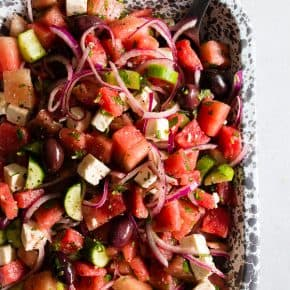 This watermelon Greek salad is a refreshing take on the classic Greek salad. Full of sweet watermelon, red onions, cucumbers, olives, feta cheese and lots of fresh herbs. You'll love this simple summer salad!