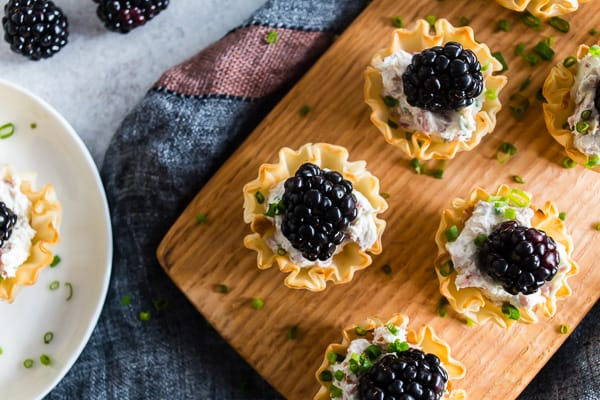 These goat cheese prosciutto blackberry phyllo bites are a delicious addition to any holiday party - tangy goat cheese mixed with cream cheese, chives, crispy prosciutto and topped with a fresh blackberry. This fun appetizer is the perfect little 2 bite treat!