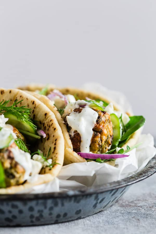 These Greek chicken meatball gyros are packed full of fresh herbs and feta cheese and topped with creamy tzatziki sauce and crunchy vegetables. They are a fun twist to traditional gyros and chicken souvlaki.