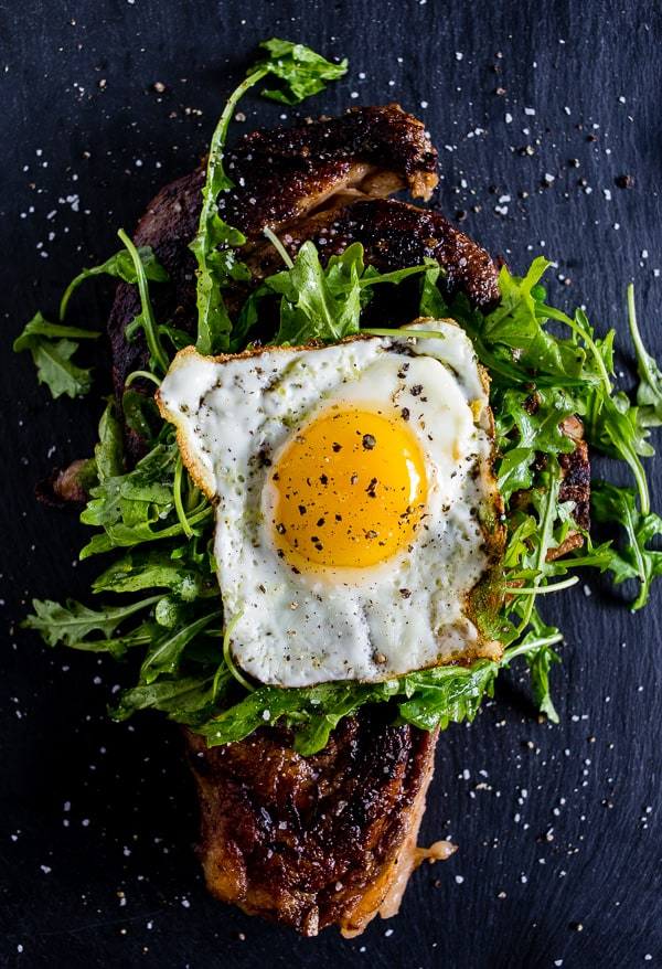 This fried egg topped grilled ribeye is your breakfast or dinner of your dreams. Deliciously seasoned steak grilled and then topped with a lightly dressed arugula salad and a super crispy around the edges fried egg. This is the type of dish you'll devour and dream about!