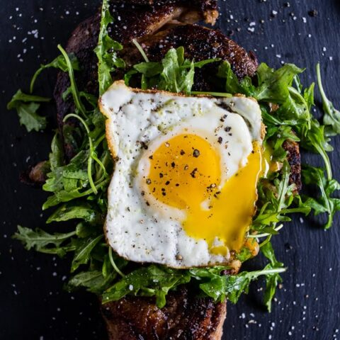 fried egg topped steak with arugula