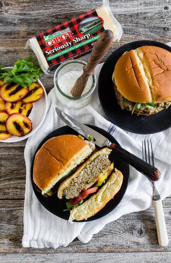 This cheesy grilled peach jalapeno turkey burger is the perfect combination of sweet and spicy. Fresh summer peaches grilled to bring out their sweetness and paired with a herb, cheese and jalapeno packed turkey burger and topped with sharp cheddar cheese and a sprinkling of cilantro. If you're a fan of sweet and heat this burger is for you!