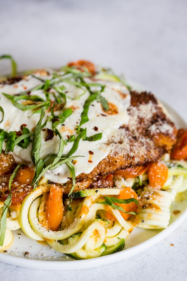 This summer chicken Parmesan with zoodles is made with fresh sauteed garlicky tomatoes, crispy chicken covered in fresh mozzarella cheese and served with fresh spiralized zucchini noodles. It's a fresh spin to the traditional recipe and the perfect use for all those summertime vegetables.