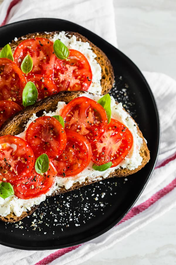 This ricotta tomato toast is my favorite way to start the day. Crunchy toasted whole wheat sourdough spread with creamy ricotta cheese and topped with sun-ripenedtomatoes, kosher salt, and black pepper. For an extra boost of flavor add some fresh basil leaves.
