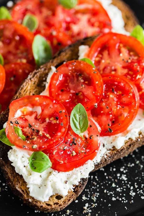 This ricotta tomato toast is my favorite way to start the day. Crunchy toasted whole wheat sourdough spread with creamy ricotta cheese and topped with sun-ripened tomatoes, kosher salt, and black pepper. For an extra boost of flavor add some fresh basil leaves.