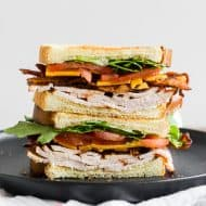 This turkey and cheese BLT sandwich is the perfect back to school sandwich. It combines lightly toasted bread with a homemade garlic basil mayonnaise, sliced turkey, sharp cheddar cheese, crispy bacon, sliced tomato and baby arugula. It's flavorful, easy to make and a step above your everyday bagged lunch sandwich.