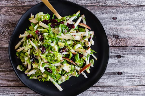 This tangy Brussels sprout apple slaw is a great addition to your fall menu. Crispy shaved Brussels sprout combined with dried cranberries, and apples all tossed in a homemade shallot whole grain mustard vinaigrette. You'll love this simple side dish!
