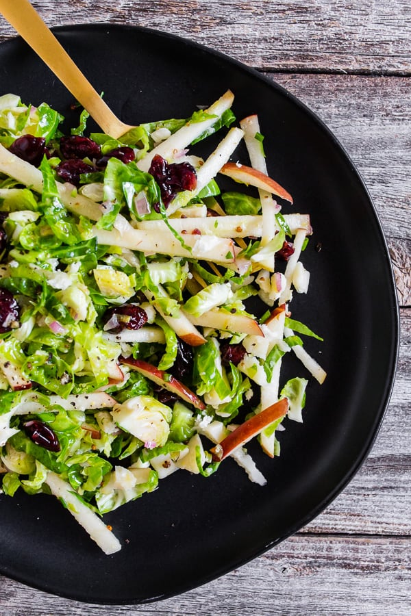 This tangy Brussels sprout apple slaw is a great addition to your fall menu. Fresh shaved Brussels sprouts combined with dried cranberries, crumbled Parmesan cheese, and apples all tossed in a homemade shallot whole grain mustard vinaigrette. You'll love this simple side dish!