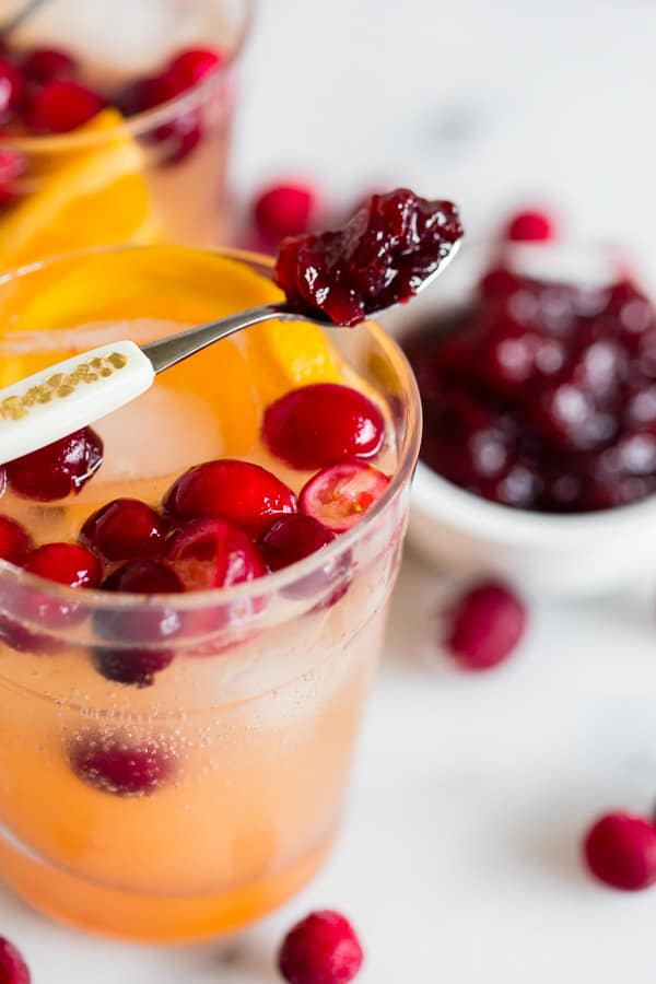 This cranberry gin fizz is a great addition to your holiday cocktail rotation. Made with gin, fresh squeezed orange juice, homemade whole berry cranberry sauce and a splash of fizzy water. You'll love this simple winter cocktail.