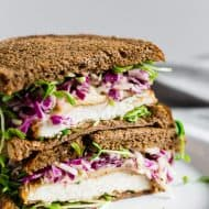 This crispy chicken sandwich with cabbage apple slaw takes the flavors of fall and puts them into a sandwich. It's a perfectly cooked crispy chicken cutlet topped with smoked Gouda cheese, pea shoots, and a homemade tangy red cabbage apple slaw. You'll love this killer sandwich.