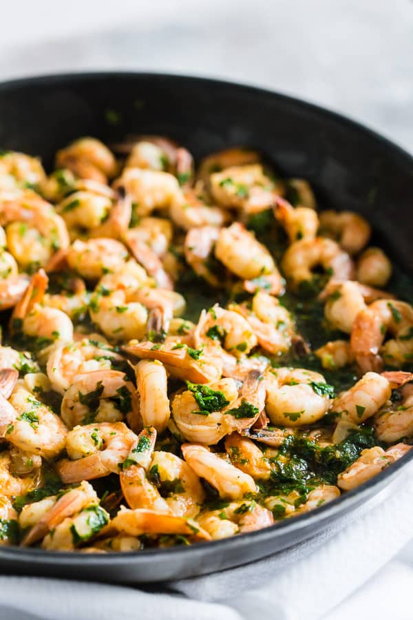 This spicy garlic cilantro shrimp is the perfect easy dinner or party appetizer. Made with spicy cayenne olive oil, dry sherry, lots of thinly sliced garlic, garlic chili sauce, wild-caught shrimp and lots of fresh cilantro. You'll love this quick and easy dish!