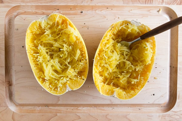 two spaghetti squash halves shredded on a cutting board