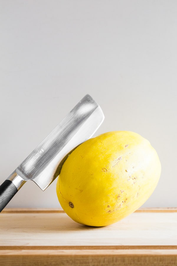 spaghetti squash on a cutting board with a knife in the flesh