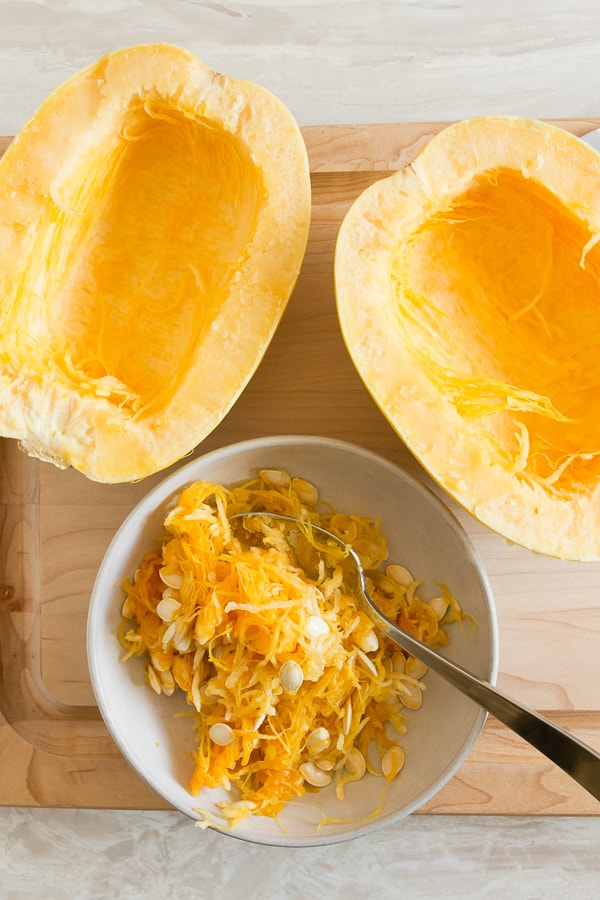 spaghetti squash cut in half on a cutting board with a bowl full of seeds