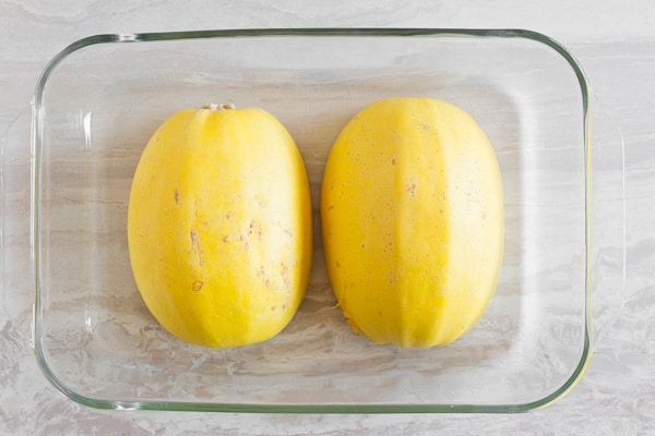 spaghetti squash halves in a glass dish