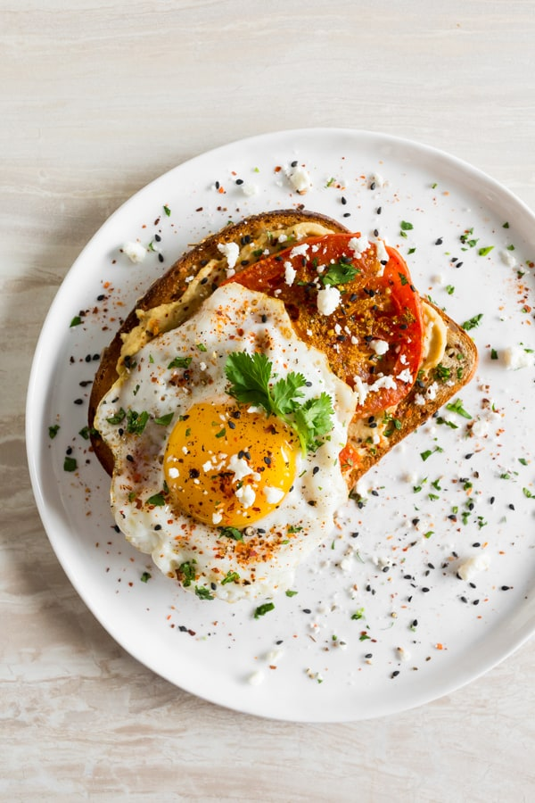 This shakshuka hummus toast is a healthy and flavorful way to start the day. Middle eastern spiced roasted tomatoes served on top of hummus toast with a runny egg, fresh herbs, and salty feta cheese.