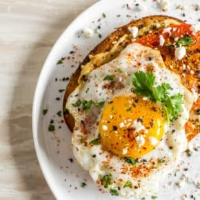 Shakshuka hummus toast topped with ras el hanout roasted tomatoes, fried egg, fresh cilantro, and tangy feta cheese. Simple and delicious!