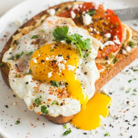 This shakshuka hummus toast is a healthy and hearty breakfast. Hummus spread toast topped with spiced roasted tomatoes, fried egg, cilantro and feta cheese.