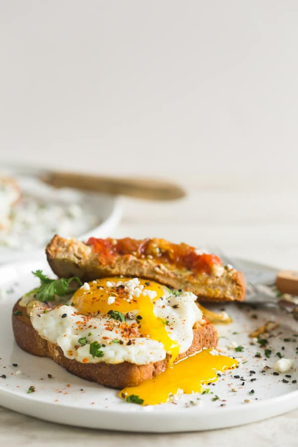 This shakshuka hummus toast is the perfect breakfast!. Ras el hanout roasted tomatoes served with fried egg, cilantro, and feta cheese.