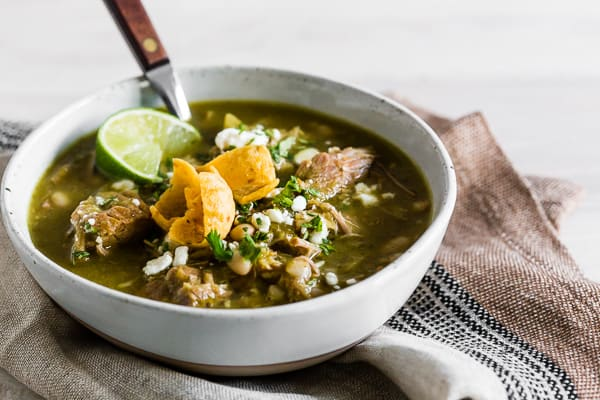 This Instant Pot pork chili verde is packed full of tomatillos, cilantro, diced green chiles, fork-tender pork shoulder, and white beans. It's perfect for cold snowy days and tastes great when topped with Cotija cheese, cilantro, and crispy corn chips.