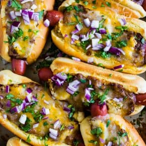 These oven baked chili cheese dogs are the perfect party meal! Made right on a sheet pan and then oven baked until hot and melty.