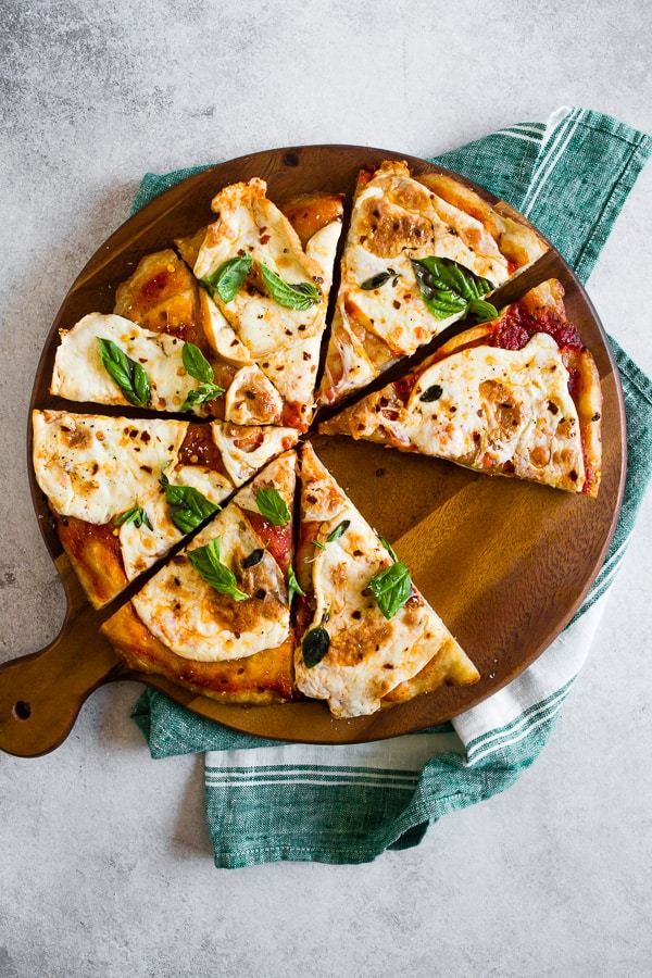 This smoked mozzarella pizza is topped with a light layer of marinara sauce, freshly smoked mozzarella cheese, fresh herbs and a sprinkle of grated Parmesan. It's packed full of flavor and cooks in just about 20 minutes.
