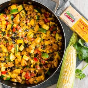 This Tex Mex chicken and vegetable skillet is ready in just 30 minutes and a great way to use up all of those summer vegetables. It's packed full of zucchini, yellow squash, sweet summer corn, bell peppers, seasoned chicken and topped with the just the right amount of spicy Cabot habanero cheddar cheese. Serve alone or piled high on rice. Either way, it's totally delicious!