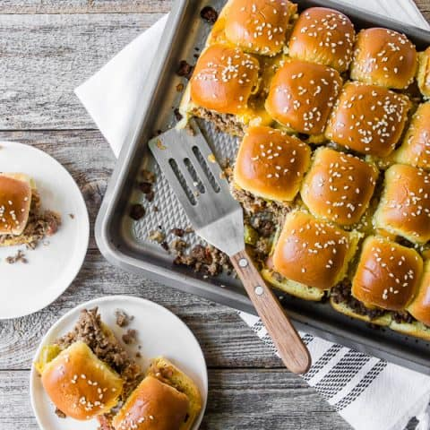 baked bacon cheeseburger sliders on a sheet pan and plate