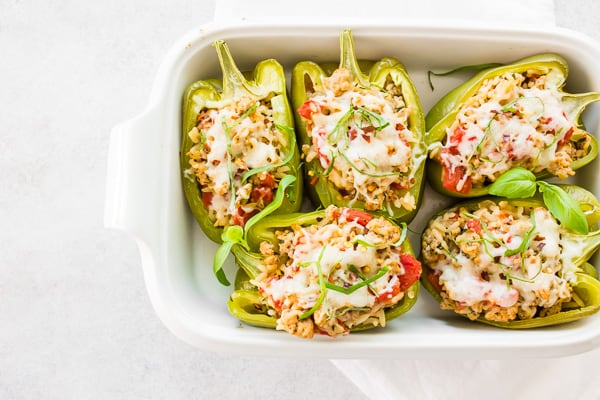 ground chicken stuffed bell peppers in a white dish