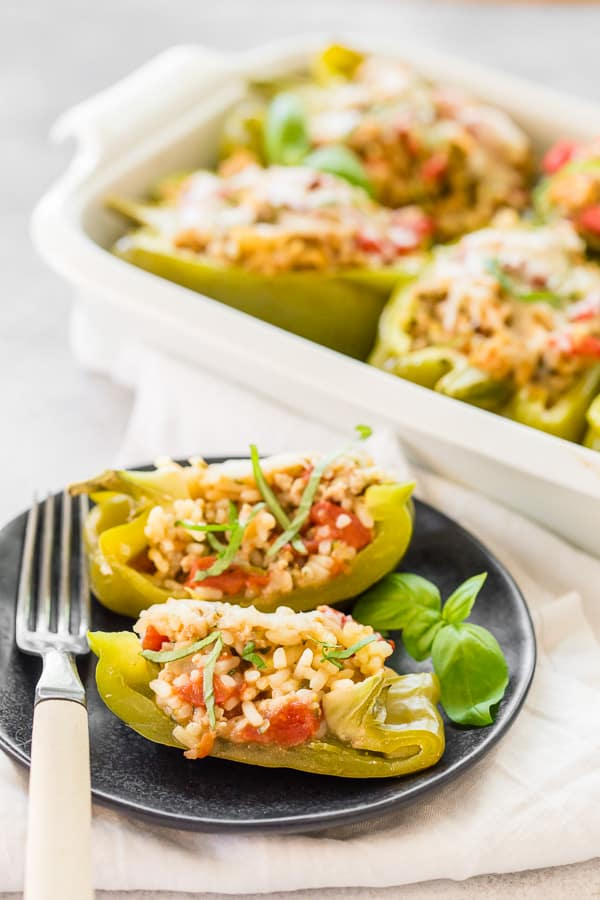 ground chicken stuffed bell peppers cut in half and sitting on a small plate with a fork