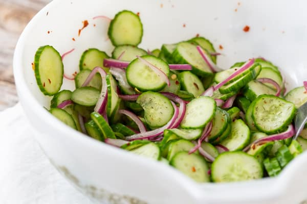 sliced cucumber salad in a white bowl with red onion