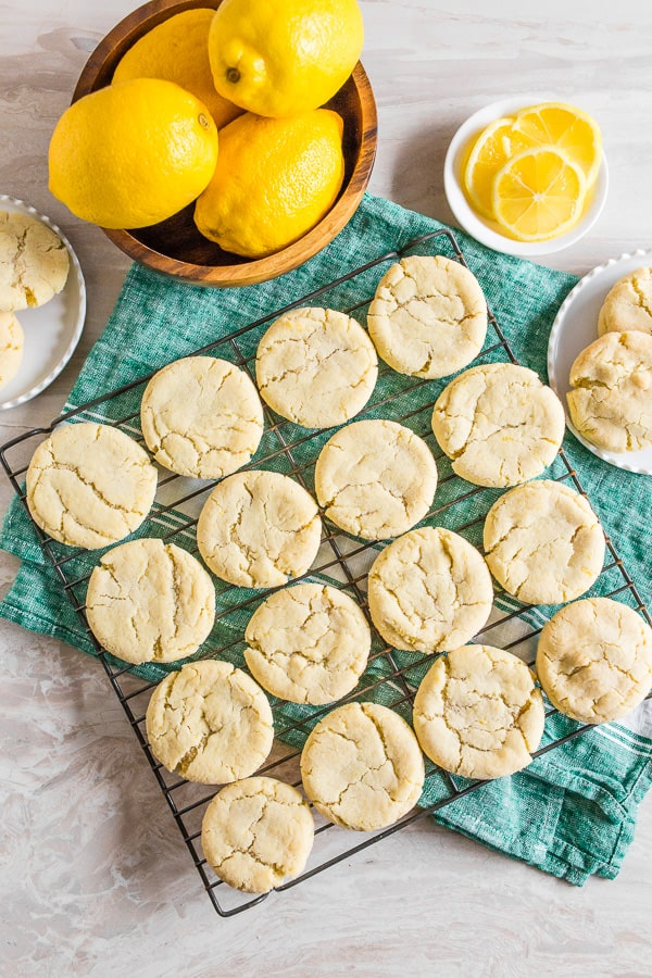 vanilla bean lemon sugar cookies on a tray with fresh lemon surrounding the cookies