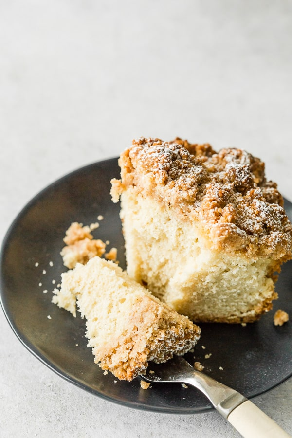 sourdough discard cinnamon crumb cake on a black pate with a bite sitting on a fork