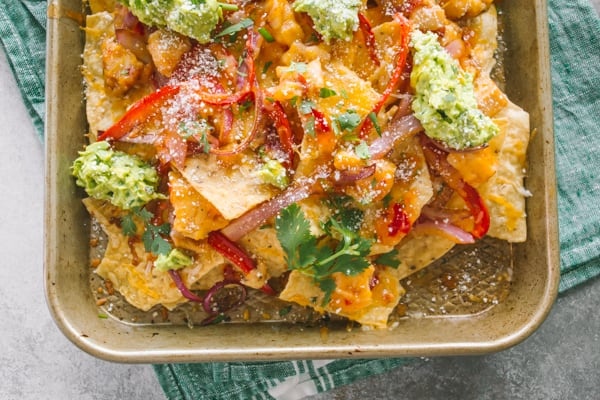 sweet chili chicken nachos topped with fresh avocado and cilantro