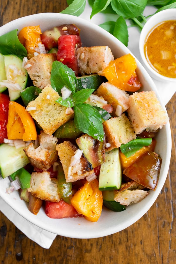 grilled sourdough panzanella salad in a white bowl with dressing on the side
