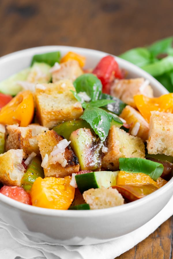grilled sourdough panzanella salad in a white bowl with fresh basil