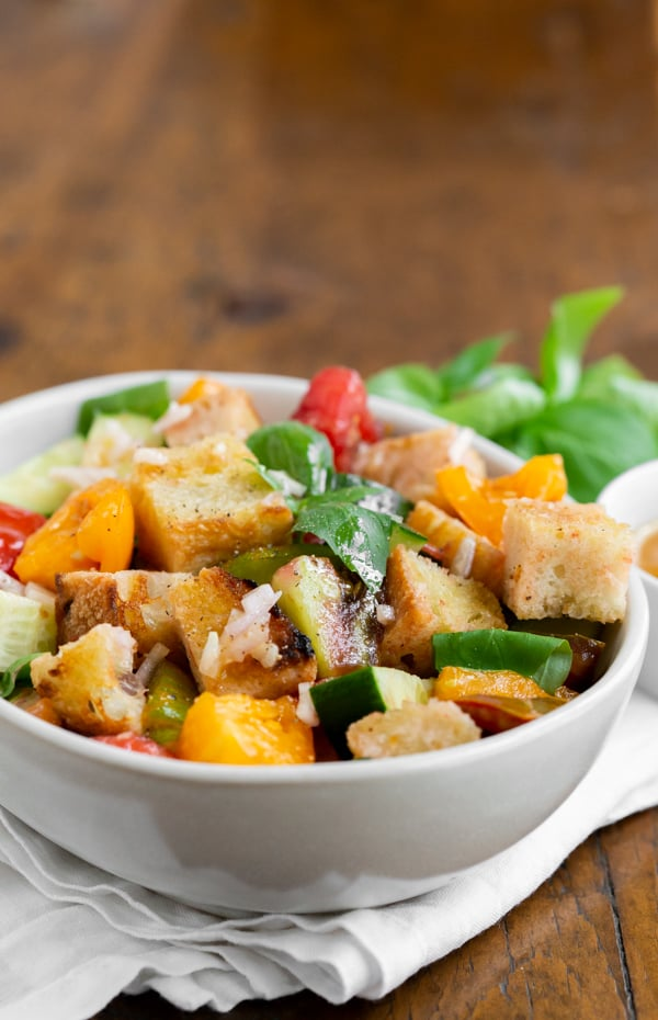 grilled sourdough panzanella salad in a white bowl