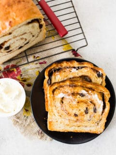 sliced cinnamon raisin sourdough bread on a plate with butter