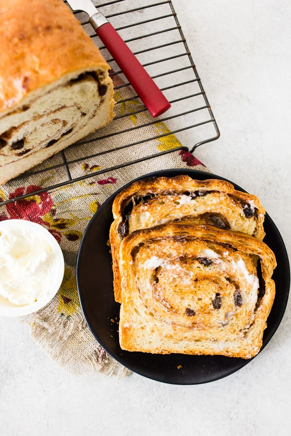 toasted cinnamon raisin sourdough bread on a plate with butter