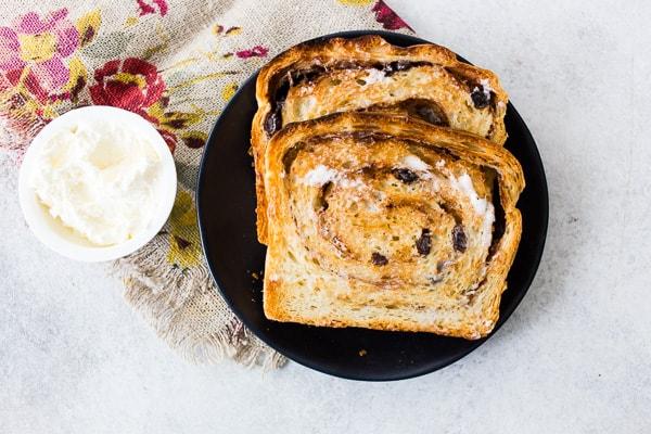 sliced cinnamon raisin sourdough bread sliced on a plate with butter