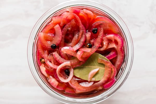 overhead shot of pickled red onions in small glass jar