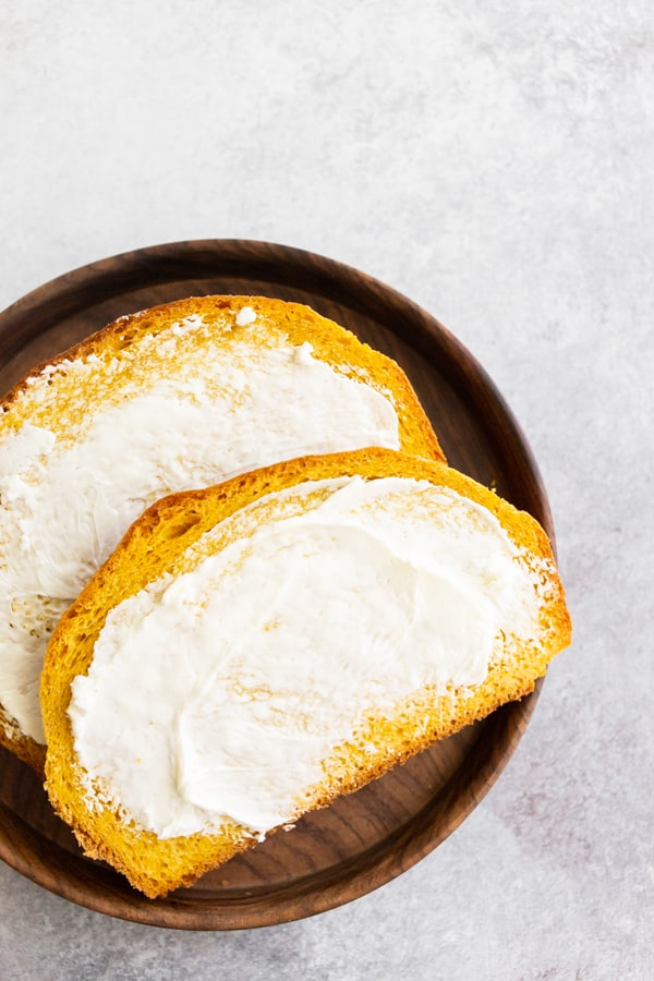 Pumpkin Yeast Bread sliced on a plate with butter