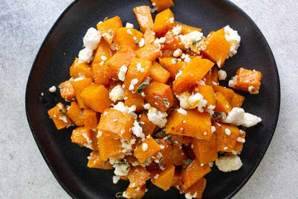 honey roasted butternut squash on a black plate sprinkled with goat cheese