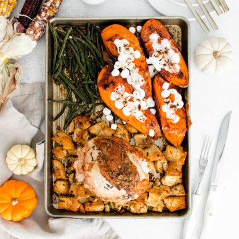 sheet pan thanksgiving dinner on a sheet pan surrounded by fall decor