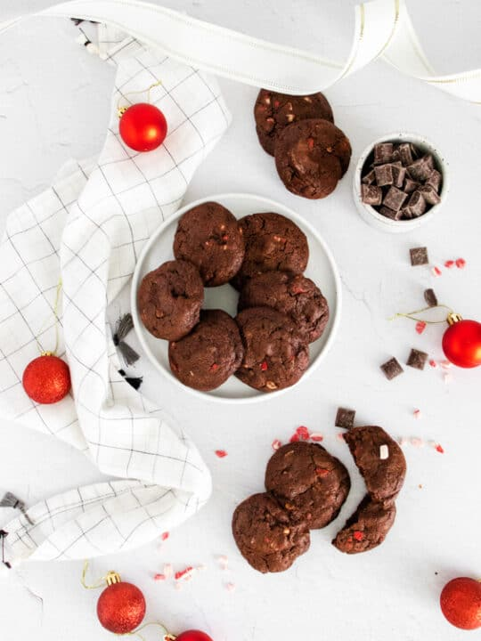 chocolate peppermint bark cookies on a white table surround by chocolate chips