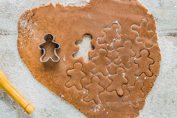 soft gingerbread cutout cookies getting cut out with cookie cutters